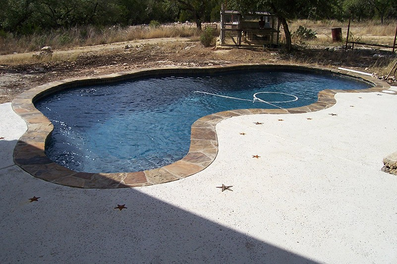 unfinished pool with debris on one side