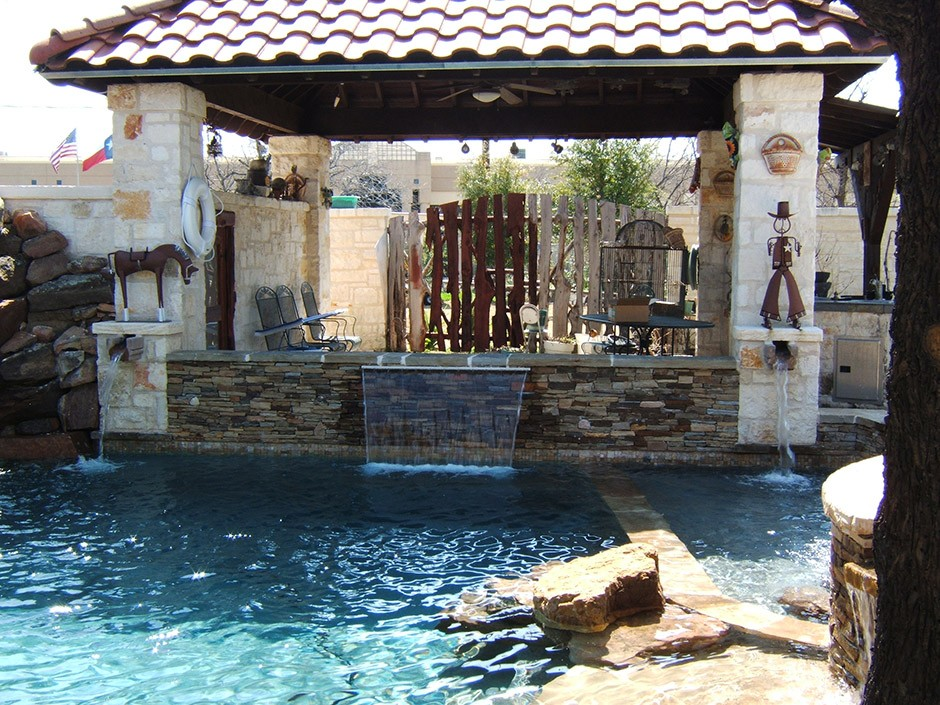 pool with a fence and waterfall