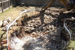 a bulldozer digging in a backyard