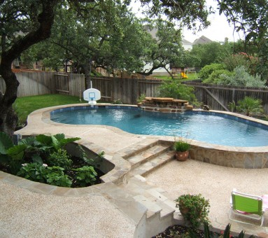 swimming pool with a small basketball goal and stone work