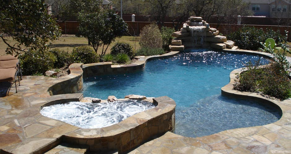 suburban looking back yard with a swimming hole and jacuzzi