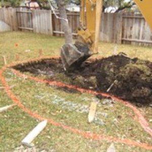 excavator digging up a large mound of dirt