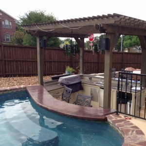 outdoor kitchen next to a pool